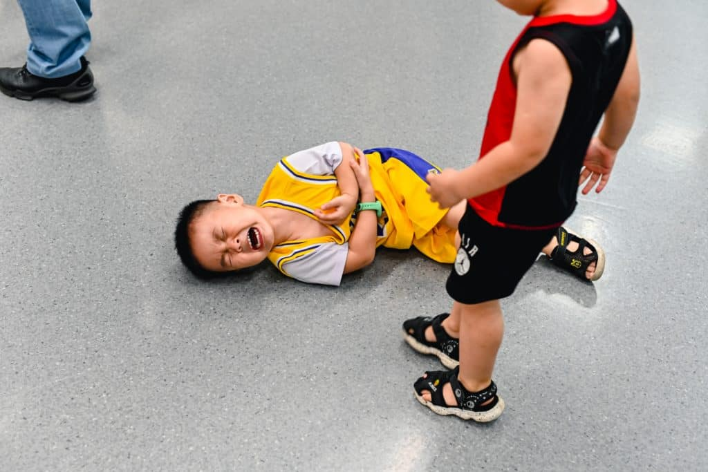 mental health activities for primary school - young boy who is standing and looking at another young boy who is in pain