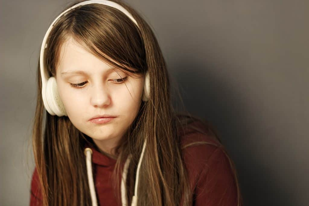 mental health activities for primary school - girl listening to music on white headphones