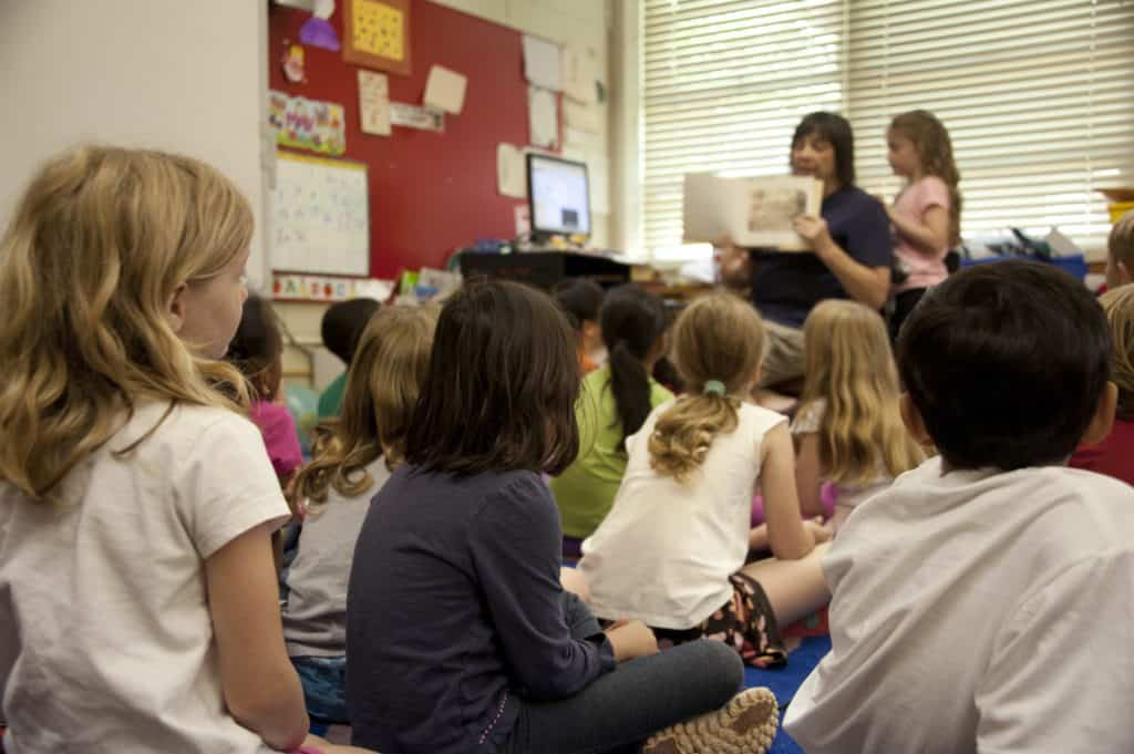 mental health activities for primary school - a classroom of sitting children looking up at a teacher who is reading a picture book