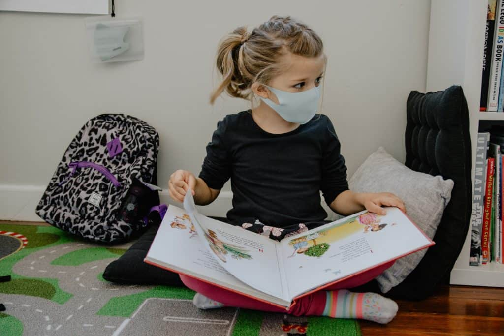mental health activities for primary school - young girl wearing a face mask and reading a large book on her lap