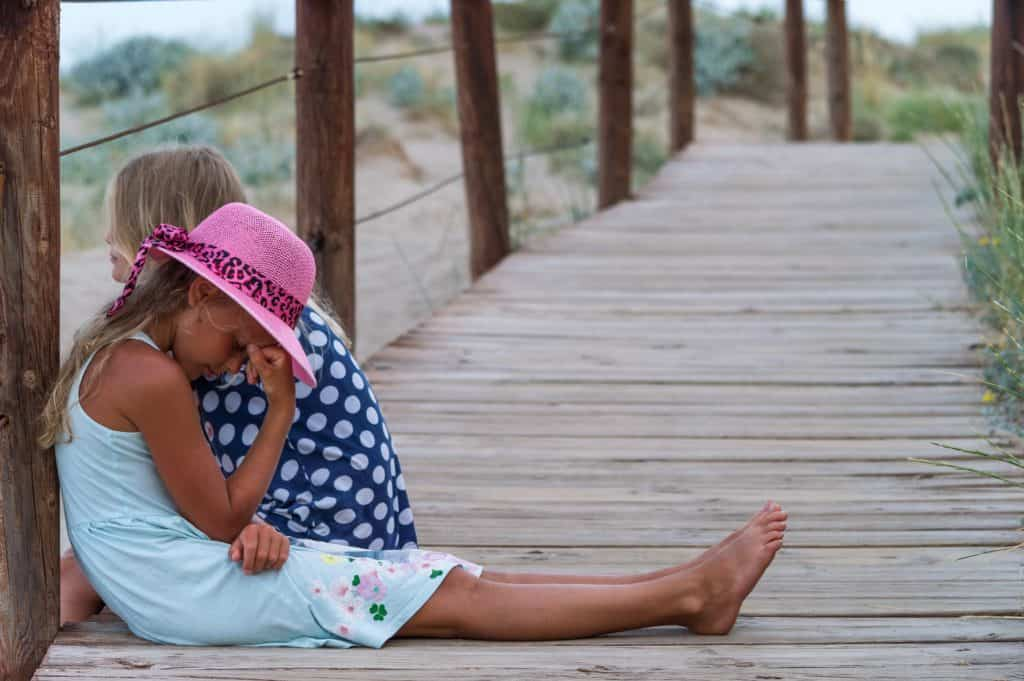 mental health activities for primary school - 2 girls sitting on a wooden beach path, one is distressed and holding her head in her hand, the other is looking out onto the beach